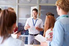 LärareWith College Students anseende vid skrivbord i klassrum Fotografering för Bildbyråer