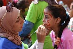 Lärarinna i den head halsduken på skolan som samlar flickorna i cirkel och drar på sanden Arkivfoton