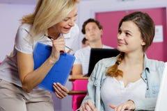 Lärarinna som talar med den kvinnliga studenten royaltyfri fotografi