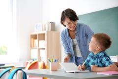 Lärarinnaportionbarn med uppgift arkivfoton