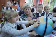 Lärarinnavisningjordklot till barn arkivfoton