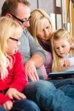 Läs- berättelse för familj i bok på soffan i hem Royaltyfria Bilder