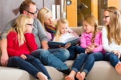 Läs- berättelse för familj i bok på soffan i hem royaltyfria foton