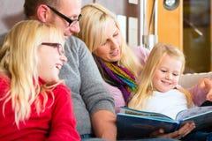 Läs- berättelse för familj i bok på soffan i hem Royaltyfri Fotografi