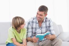 Läs- berättelse för lycklig fader för pojke på soffan Royaltyfria Foton