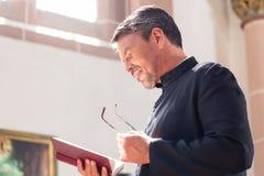 Läs- bibel för katolsk präst i kyrka arkivbilder