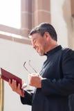 Läs- bibel för katolsk präst i kyrka royaltyfri bild