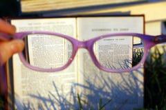 Läs- bibel till och med exponeringsglas Arkivbilder