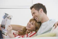 Läs- broschyr för gladlynta och avkopplade par på soffan Arkivbilder