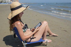 Läs- ebook för flicka på stranden arkivfoton