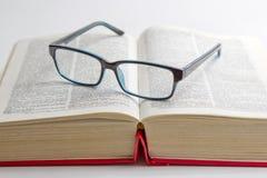 Läs- exponeringsglas som förläggas på en bok Royaltyfria Bilder
