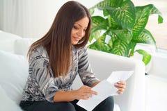 Läs- goda nyheter för lycklig entreprenörkvinna i en bokstav på soffan arkivfoton
