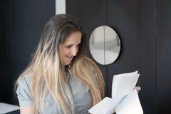 Läs- goda nyheter för lycklig entreprenörkvinna i en bokstav på soffan royaltyfria foton