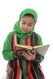 Läs- helig Quran för liten ung muslimsk flicka Arkivfoton