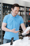 Läs- information om nyfiken manlig kund om telefonen på elektroniklagret Arkivfoto