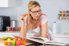 Läs- kokbok för mogen kvinna i kök som söker efter recept arkivfoton
