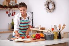 Läs- kokbok för ung kvinna i köket, arkivbild