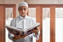 Läs- Koranen för muslimsk man inom moské Royaltyfria Bilder