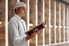 Läs- Koranen för muslimsk man inom moské Arkivfoton