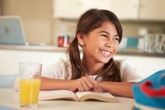 Läs- läxa för latinamerikansk flicka på tabellen royaltyfria foton