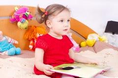 Läs- liten flicka i säng Fotografering för Bildbyråer