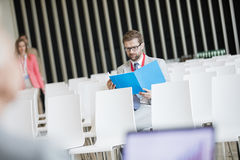 Läs- mapp för affärsman, medan sitta i seminariumkorridor på konventcentret Arkivfoto