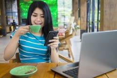 Läs- meddelande för kvinna, medan tycka om kaffe Arkivfoto