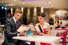 Läs- meny för lyckliga par i restaurang Arkivbild