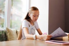 Läs- meny för modern flicka, medan sitta nära fönster i kafé Royaltyfri Foto