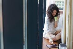 Läs- morgonnyheterna för kvinna på den digitala minnestavlan Arkivbild
