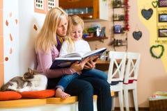 Läs- nattberättelse för moder till ungen hemma Arkivbild