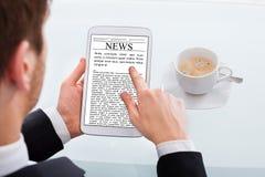 Läs- nyheterna för affärsman på den digitala minnestavlan på skrivbordet Arkivbild