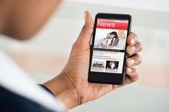 Läs- nyheterna för kvinna på mobiltelefonen Arkivfoton