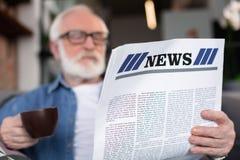 Läs- nyheterna för mogen gentleman med kaffe fotografering för bildbyråer