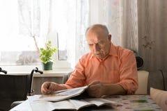 Läs- nyheternauppdateringar för gammal skallig man på tabloidtidningen royaltyfri foto