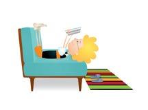 Läs- pojke på en soffa Arkivfoto