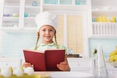 Läs- recept för gullig flicka för att laga mat royaltyfri foto