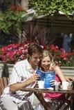 Läs- resehandbok för lyckliga par på det utomhus- kafét royaltyfria foton