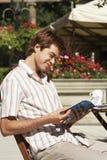 Läs- resehandbok för man på det utomhus- kafét arkivbild
