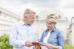 Läs- resehandbok för medelåldersa par utanför byggnad fotografering för bildbyråer