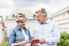 Läs- resehandbok för medelåldersa par utanför byggnad arkivbild