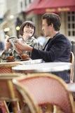Läs- resehandbok för par på det utomhus- kafét royaltyfria foton