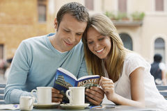 Läs- resehandbok för par på kafét arkivfoton