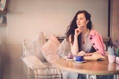 Läs- roman för härlig dam i ett kafé Arkivfoton