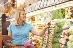 Läs- shoppinglista för kvinna från den Digital minnestavlan i supermarket royaltyfri bild