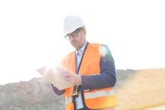 Läs- skrivplatta för manlig arbetsledare på konstruktionsplatsen på solig dag Royaltyfria Bilder