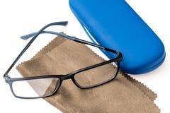 Läs- svart glasögon, brun microfiberlokalvårdtorkduk och blått skyddande fall Royaltyfri Foto