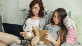 Läs- textbok för liten gullig dotter som gör läxa för grundskola medan hennes älska moder som bläddrar och arbetar stock video
