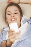 Läs- textmeddelande för kvinna på en mobiltelefon Royaltyfri Foto
