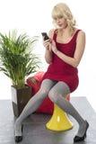 Läs- textmeddelande för ung kvinna genom att använda mobiltelefonen Royaltyfria Foton